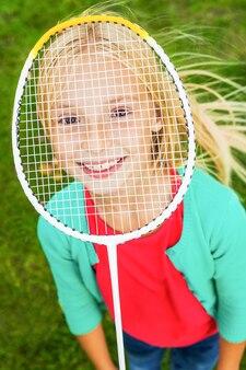 プレイする準備ができました!バドミントンラケットの後ろに顔を隠し、緑の芝生の上に立って笑っているかわいい女の子の上面図