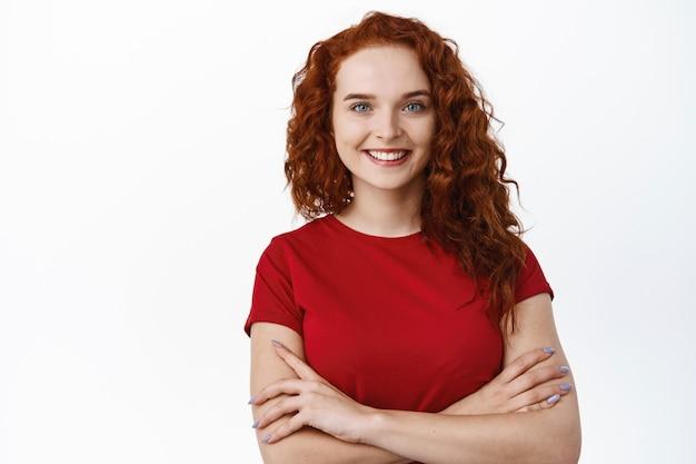 私は信頼できます。巻き毛の赤い髪と良い肌の状態、自然な白い笑顔、胸に腕を組んで、決意を持って見える、白い壁を持つ自信のある若い女性