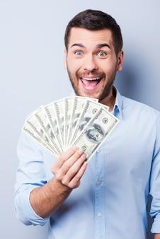 Я богатый! счастливый молодой человек держит бумажную валюту и смотрит в камеру, стоя на сером фоне