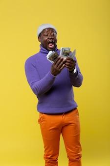 びっくりしました。黄色の背景の上に立って、彼のお金を見つめている陽気な男性の人