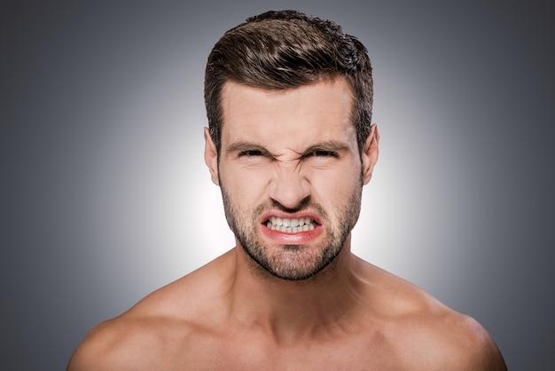 너무 화가 나! 회색 배경에 서 있는 동안 카메라를 보고 찡그린 셔츠를 입지 않은 분노한 젊은 남자의 초상화