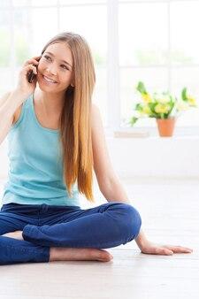 Я так рада тебя слышать! веселая девочка-подросток разговаривает по мобильному телефону и улыбается, сидя на полу в своей квартире
