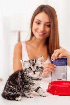 너무 배고파요! 귀여운 스코틀랜드 폴드 고양이가 카메라를 쳐다보는 동안 젊은 여성이 고양이 먹이를 배경으로 팩을 여는 동안