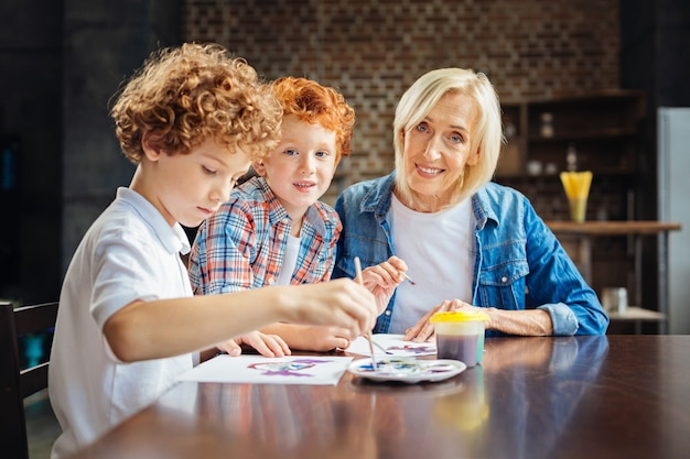 Я так ими горжусь. избирательный фокус на улыбающейся пожилой женщине и ее очаровательном рыжем внуке, смотрящих в камеру, сидя рядом с другим внуком