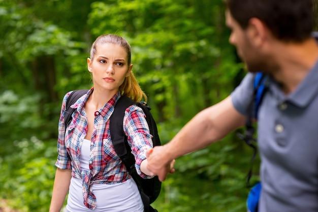 私は疲れている!彼女のボーイフレンドの手を握り、森の中を歩きながら否定性を表現するバックパックを持つ疲れた若い女性