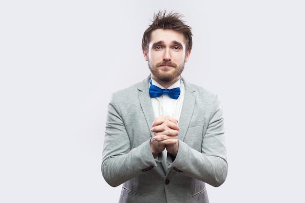 죄송합니다, 용서해 주세요. 캐주얼한 회색 양복과 파란색 나비 넥타이를 한 슬픈 수염 난 남자가 카메라를 보고 도움이나 용서를 구합니다. 밝은 회색 배경에 격리된 실내 스튜디오 촬영.