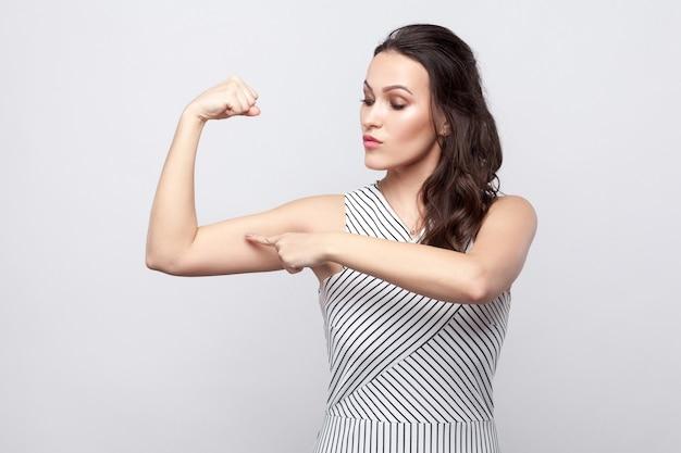 Я сильный. портрет гордой красивой молодой женщины брюнетки с макияжем и полосатым платьем, стоящим и указывающим на ее бицепс. крытая студия выстрел, изолированные на сером фоне.