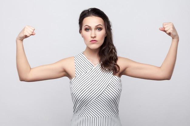 Я сильный. портрет гордой серьезной красивой молодой женщины брюнетки с макияжем и полосатым платьем, стоящим, смотрящим в камеру и показывающим ее бицепсы. крытая студия выстрел, изолированные на сером фоне.