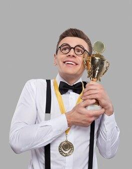 Я лучший! веселый молодой человек в галстуке-бабочке держит трофей и смотрит вверх, стоя на сером фоне
