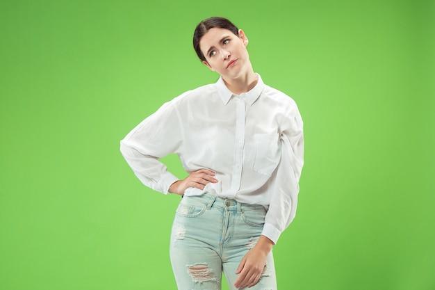 Я устал от всего. скучающая женщина. скучная, скучная, утомительная концепция. молодая довольно кавказская эмоциональная женщина. человеческие эмоции, концепция выражения лица. студия, изолированные на модном зеленом фоне