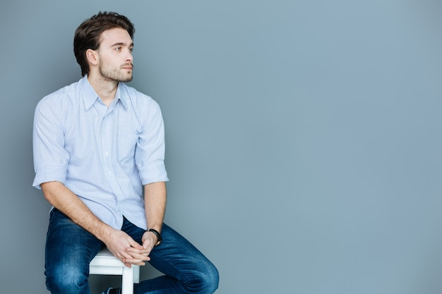 Я устал. приятный грустный молодой человек, сидящий на стуле и держащий руки вместе, думая о своей жизни