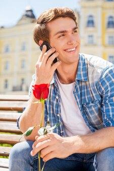 Я жду тебя! счастливый молодой человек держит одну розу и разговаривает по мобильному телефону, сидя на скамейке