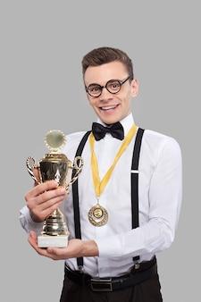 Я победитель! веселый молодой человек в галстуке-бабочке держит трофей и улыбается, стоя на сером фоне