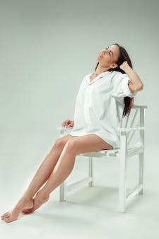 나는 젊고 예쁘다. 회색 스튜디오 배경에 아름 다운 검은 머리 여자의 초상화. 패션 백인 여자. 젊은 패션 모델의 초상화입니다. 긴 머리. 갈색 눈