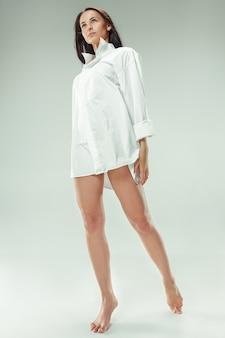 나는 젊고 예쁘다. 회색 스튜디오에 아름 다운 검은 머리 여자의 초상화