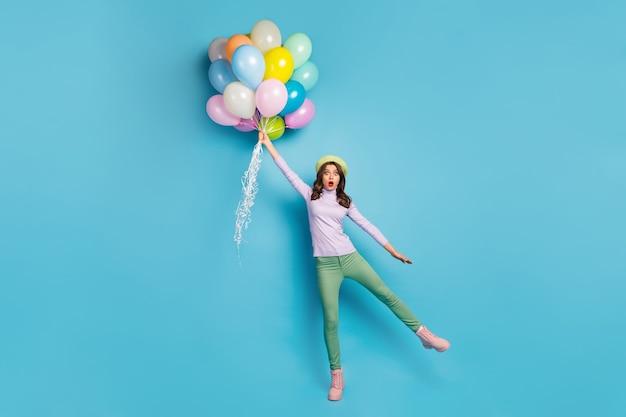 나는 내가 날 수 있다고 믿는다! 예쁜 아가씨의 전신 사진은 다채로운 공기 풍선을 들고 바람이 입고 보라색 풀오버 베레모 모자 녹색 바지 신발 격리 된 파란색 벽으로 제기 충격