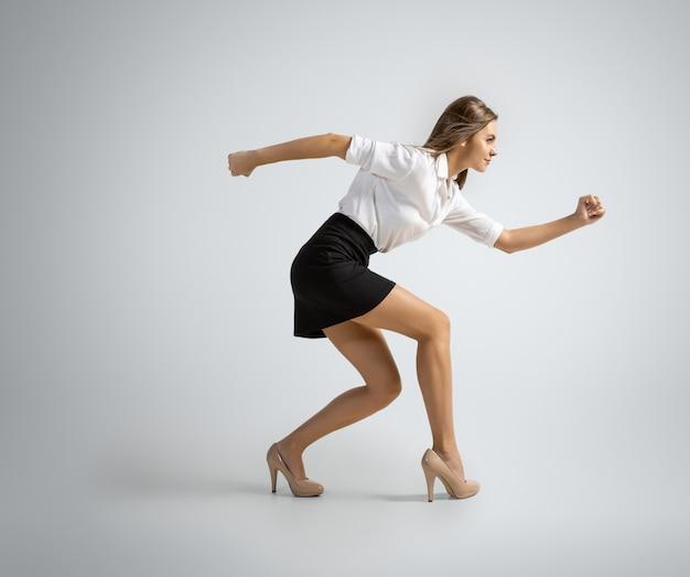 나는 모든것을 할수있다. 회색 배경에서 실행을 준비하는 사무실 옷에 행복 한 여자