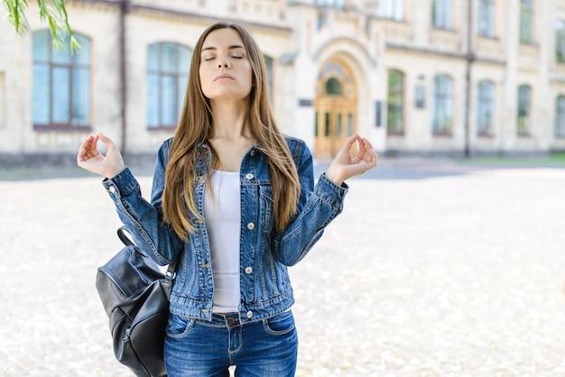 Я могу это сделать! никакого стресса, депрессии, тревоги! фотопортрет довольно сосредоточенной умной умной красивой довольной милой дамы с закрытыми глазами, делающей символ ом, пытающимся сконцентрироваться перед сдачей экзамена