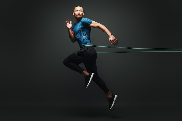 Я могу сделать это, спортсмен прыгает с лентой сопротивления на темном фоне, глядя в сторону