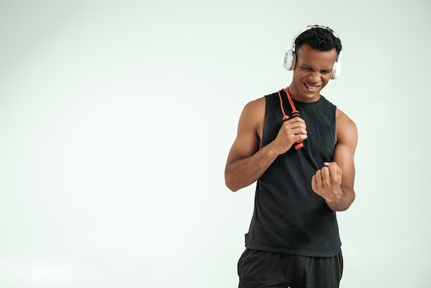 I can do everything cheerful young afro american man in headphones holding a jumping rope