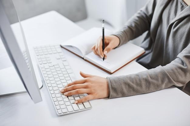 Я могу справиться с несколькими задачами. девушка обрезанного снимка успешная печатая на клавиатуре и делая примечания пока смотрящ экран компьютера и изучающ новую графику дела. нет времени на отдых