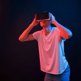 I can't believe my eyes. young man using virtual reality glasses in the dark room with neon lighting