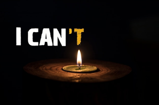 I can't - i can - white candle with dark background - in a wooden candlestick.