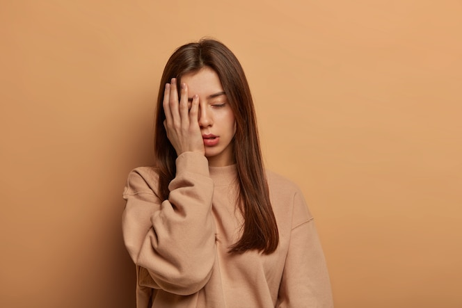 이 엉망진창을 볼 수 없습니다. 좌절 한 피곤한 여자는 얼굴에 손바닥을 만들고, 불쾌하고 무관심하며, 오랜 시간 일한 후 피곤함으로 한숨을 쉰다.