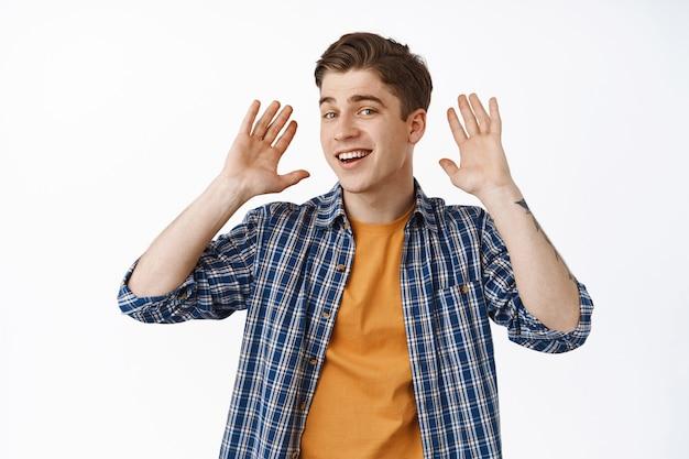 聞こえません。笑顔の若い男は耳の近くで手を握り、繰り返し尋ね、騒々しい場所に立って、聞きたくない、白の上にのんきに立っている