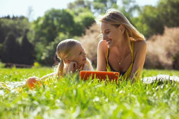 당신을 소중히 여깁니다. 태블릿을 들고 야외에서 그녀의 엄마와 이야기 귀여운 소녀