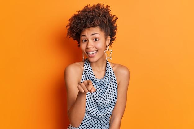 私はあなただけを選びます。ファッショナブルな服を着たポジティブなアフリカ系アメリカ人の女性が人差し指を直接あなたに向けてパーティーに招待します。鮮やかなオレンジ色の背景の上にスタイリッシュな髪型があります。
