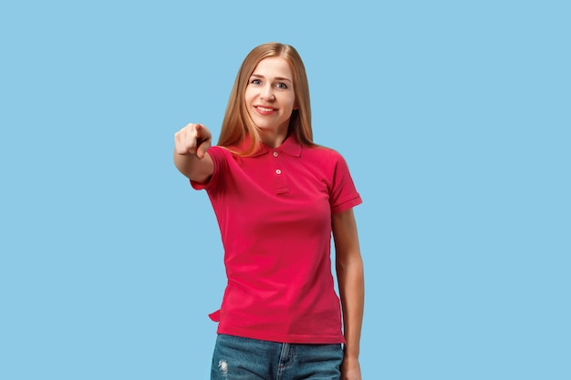 Я выбираю тебя и заказываю. улыбающаяся деловая женщина указывает вам, хочет вас, половина портрета крупным планом на синей студии