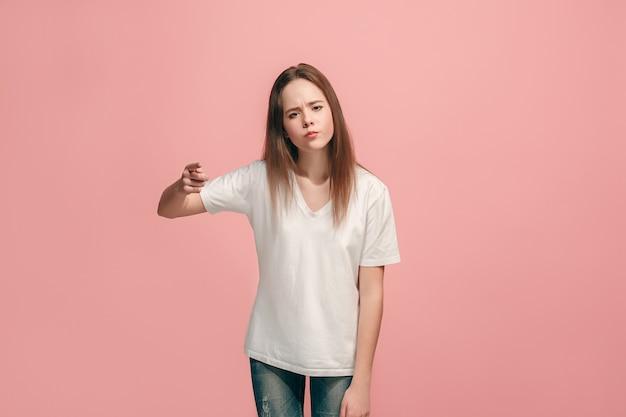 Выбираю тебя и заказываю. улыбающаяся девочка-подросток, указывая на камеру, половинный портрет крупным планом на розовом фоне студии. человеческие эмоции, концепция выражения лица. передний план. модные цвета