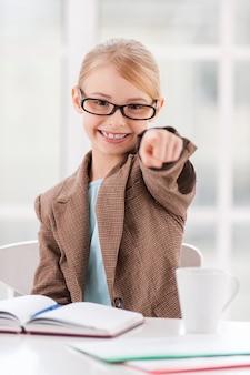 Я выбираю вас! веселая маленькая девочка в очках и формальной одежде сидит за столом и указывает вам