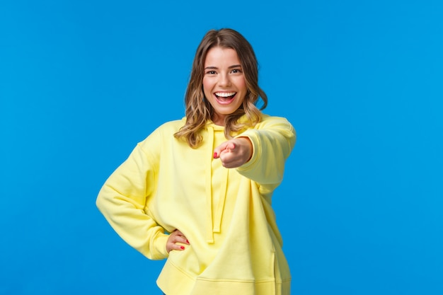 I choose you. confident and cool young blond hipster girl with short haircut, yellow hoodie, pointing finger at camera with self-assured expression making final choice, inviting join team