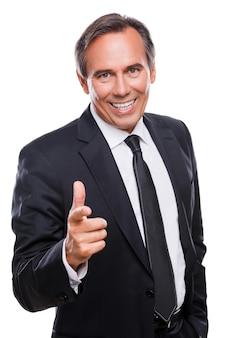 Я выбираю вас! уверенный зрелый мужчина в строгой одежде, глядя в камеру и указывая вам с улыбкой, стоя на белом фоне
