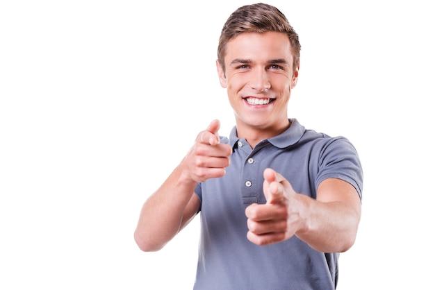 Я выбираю вас! красивый молодой человек, указывая на вас и улыбаясь, стоя на белом фоне