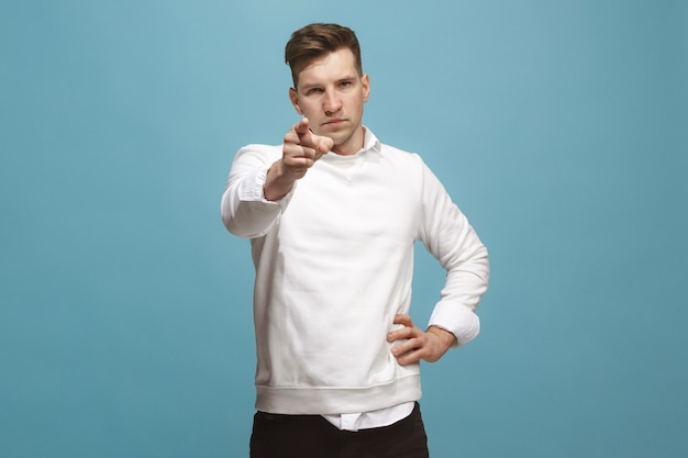 I choose you and order. overbearing businessman point you, want you, half length closeup portrait on blue studio background. the human emotions, facial expression concept. front view. trendy colors