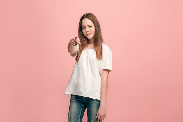 I choose you and order. the smiling teen girl pointing to camera, half length closeup portrait on pink studio background. the human emotions, facial expression concept. front view. trendy colors