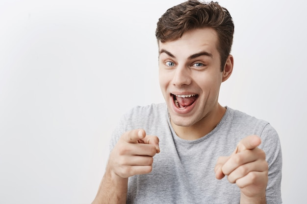 I choose you! positive emotional male with dark hair looks  with joy and points with forefingers at you. handsome young good-looking guy having fun ondoors, gestures and face expressions.