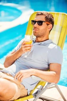 Я мог бы остаться с ней навсегда. красивый молодой человек в рубашке поло сидит на шезлонге и пьет апельсиновый сок