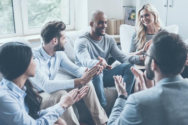 Я это сделал! группа молодых веселых людей сидит в кругу и аплодирует, пока один мужчина жестикулирует и улыбается