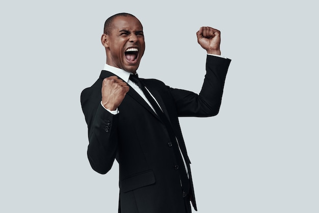 やったよ!灰色の背景に立っている間身振りと叫びの正装でハンサムな若いアフリカ人