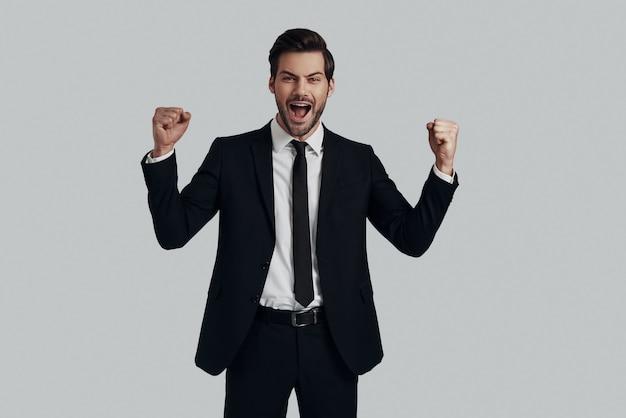 やったよ!灰色の背景に立っている間身振りと叫びのフルスーツのハンサムな若い男