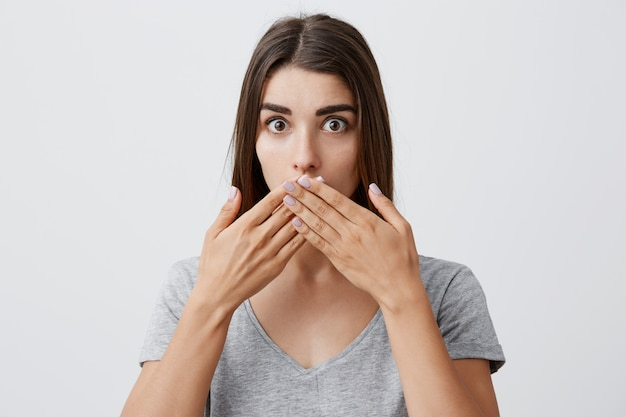 I didn't say that. beautiful young caucasian brunette girl with long hairstyle in fashionable casual gray t-shirt clothing mouth with hands,  with confused and surprised look.