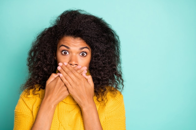 I didn't say word! closeup photo of pretty nervous dark skin lady in stupor hiding mouth holding hands near lips wear yellow knitted jumper isolated blue teal color wall