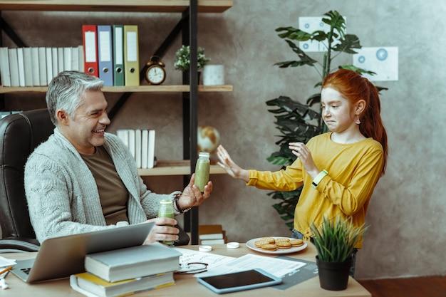 Я не хочу. милая несчастная девушка показывает гримасу, не желая пить смузи