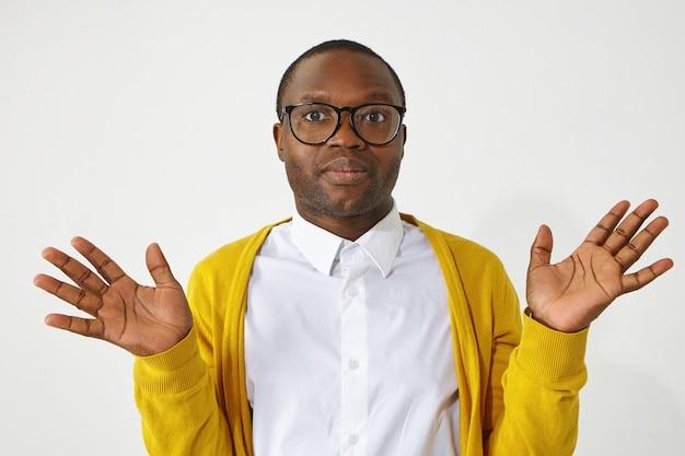 Non so, chi se ne frega, non il mio problema. ritratto di giovane maschio africano alla moda incapace in occhiali e cardigan giallo, facendo gesto indifferente o incerto. linguaggio del corpo
