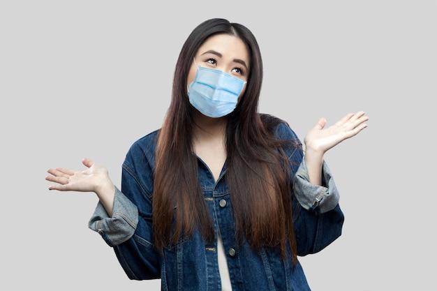 Я не знаю. путать красивая брюнетка азиатская молодая женщина с хирургической медицинской маской в синей джинсовой куртке стоя подняла руки и глядя вдумчиво. студия выстрел, изолированные на сером фоне.