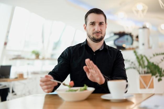 これ食べたくない!あごひげを生やした若い男は、ウェイターが彼に提供した料理に腹を立てています。男は彼のお気に入りのレストランにがっかりしている。悪い食べ物とサービスの概念。背景のレストラン。